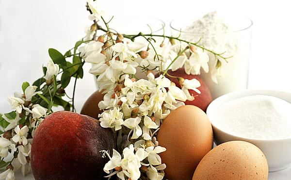 Pochi ingredienti per una preparazione semplicissima: uova, latte, farina, zucchero, fiori di robinia e pesche