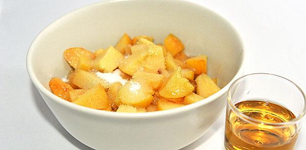Le pesche spolverate di zucchero e in ammolo nel brandy rilasciano un succo delizioso